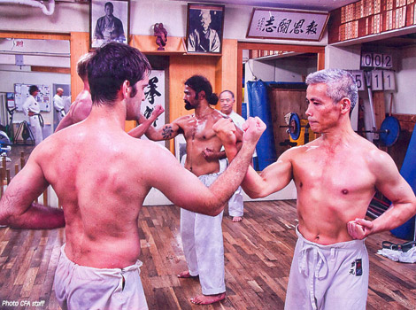 Body conditioning, in this case the repeated striking of one's arms against those of an opponent, is an essential element of karate training.